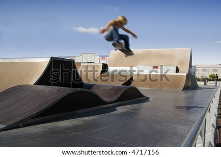 Skater doing a big air ollie in a skate park