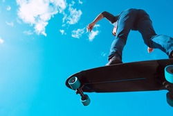 Skater in action. Man making a trick on a longboard outdoors on sunny summer day. Blue sky background. Concept of extreme sport active lifestyle