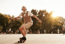 Skater posing in sunset evening on city street. Stylish hipster man with longboard ride near road on buildings background. Portrait of sport male model in urban style. Traveler. Tourist