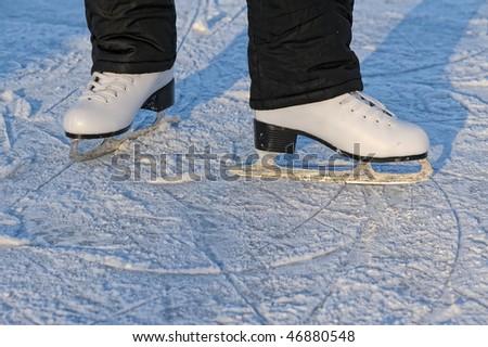 skater's legs standing on winter ice rink