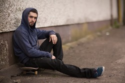 Skater taking a break outside the skate park and looking at camera sitting on his board with hood up