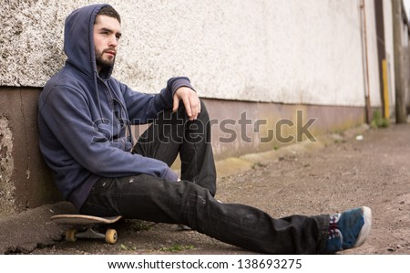 Skater with hood up sitting on his board looking thoughtful outside the skate park