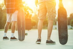Skaters friends outdoor in urban city with skateboards in their hands - Young people training longboard extreme sport - Friendship concept - Focus on right man's hand holding board - Warm filter