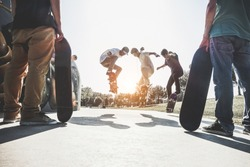Skaters jumping with skateboard in city skate park - Young guys performing tricks and skills at sunset in suburb contest - Extreme sport and youth lifestyle concept - Main focus on center guys heads