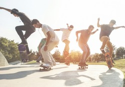 Skaters jumping with skateboard in city suburb park - Sporty guys performing tricks and skills at sunset in urban contest - Extreme sport and youth lifestyle concept - Main focus on center people