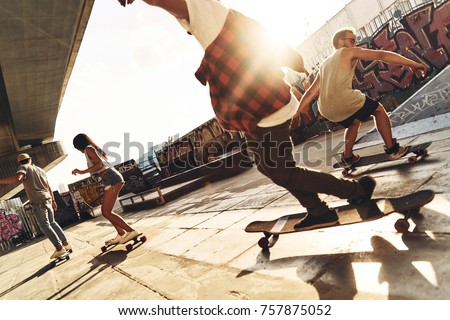 Skating is their life. Group of young people skateboarding while hanging out at the skate park outdoors