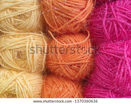skeins of colored threads of wool yarn close-up. yellow orange pink color of balls of thread. Thread with sequins, the effect of noise on the picture