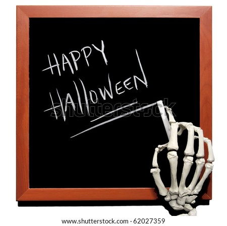 skeletal hand writes happy halloween on a blackboard