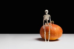 Skeleton and orange pumpkin on white table, black background side view copy space. Halloween holidays celebration. Spooky decorations. Night party. Creative horror composition. Stock photo.