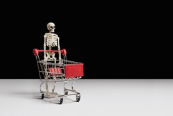 Skeleton and shopping cart on white table, black background side view copy space. Online halloween shopping concept. Holidays celebration. Spooky decor. Night party. Creative horror composition.