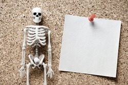 Skeleton and sticker for notes with a call to return the money. collectors intimidate borrower