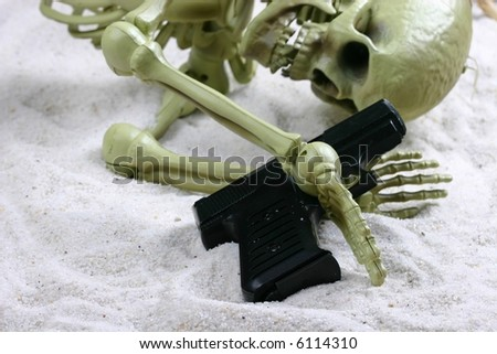 Skeleton clutching a handgun - stock photo
