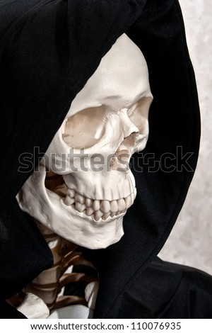 Skeleton face in a black grim reaper hood