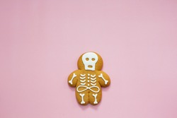 Skeleton gingerbread cookie on a pink background. Halloween trick or treat cookies