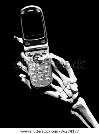 Skeleton hand holding a generic cell phone with a blank screen, isolated on black
