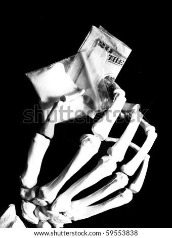 skeleton hand holds drug baggie and money