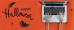 Skeleton hands typing in laptop and Happy Halloween text