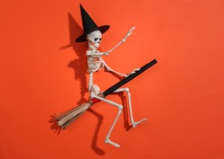 Skeleton in a witch's hat on a broomstick. Orange bright background. Halloween minimalistic concept. Top view. Flat lay