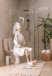 Skeleton in bathrobe sitting on toilet bowl