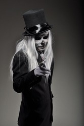 Skeleton man with long gray hair in black tailcoat and a white shirt near the  background