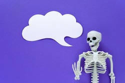 Skeleton on violet background with white blank paper cloudy speech bubble. Anatomical plastic model human skeleton with talk text balloon. Empty dialog cloud, mockup, copy space. Purple Halloween.