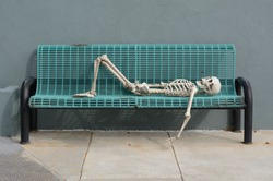 Skeleton reclining on blue bench with arm dangling down and knees bent