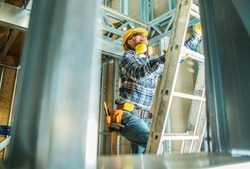Skeleton Steel Building Construction Worker Wearing Safety Hard Hat and Noise Reduction Headphones. Going Up Using Ladder.
