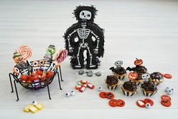 skeleton with spider web and halloween cupcakes