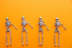 Skeletons in silver and gold are dancing on an orange background. Halloween and Day of the Dead concept