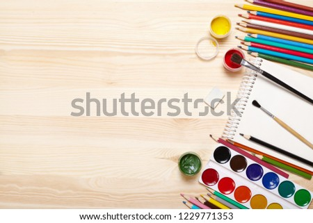 Sketchbook and drawing equipment on wooden table. #1229771353