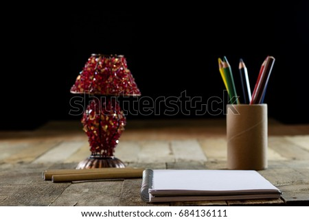 Sketchbook on old table with old sensual lamp. Black background and old table #684136111