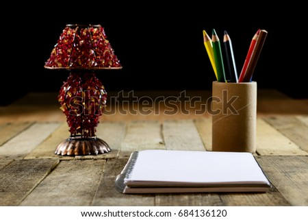 Sketchbook on old table with old sensual lamp. Black background and old table #684136120