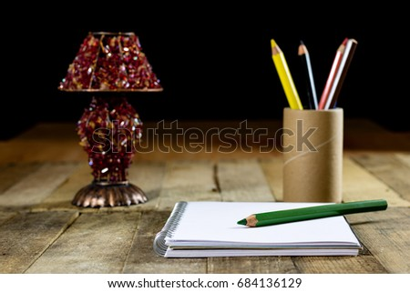 Sketchbook on old table with old sensual lamp. Black background and old table #684136129