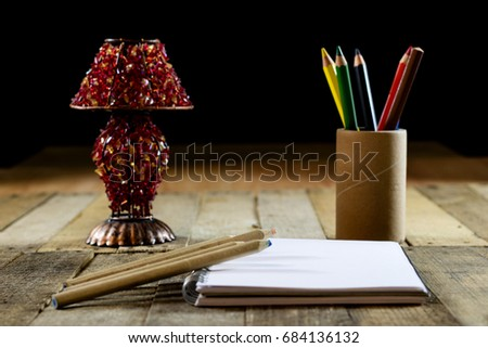Sketchbook on old table with old sensual lamp. Black background and old table #684136132