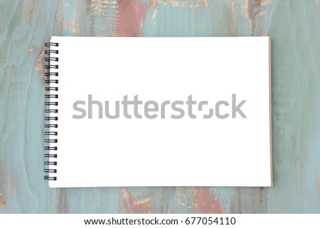 Sketchbook on teal colored wooden board