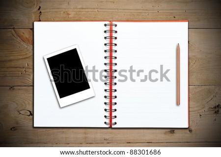 Sketchbook with photo on wooden floor