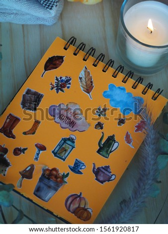 """Sketchbook with the caption in English """"Hello Autumn"""", orange page of sketchbook depicting items of Autumn theme: pumpkins, mushrooms, apples, cloud, yellow leaves, teapots, boots, scarf, sock,candle"""