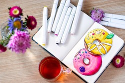 Sketching donuts in notebook. All placed on wooden table with a transparent cup of tea, notebook, markers, and flowers. Hobby. Drawing donuts. Top view. Soft focus