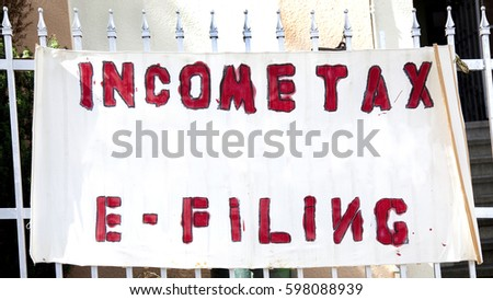 Sketchy INCOME TAX E-FILING banner on fence. Anyone can do it. Just hang out a sign. #598088939