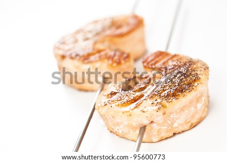 skewer of grilled seasoned salmon isolated over white background
