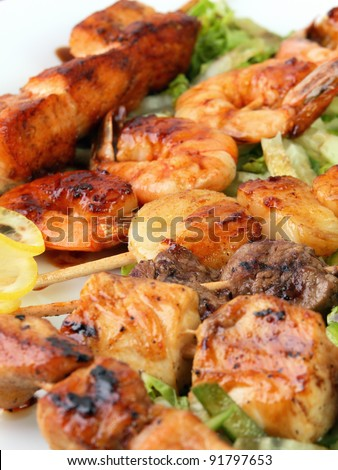 skewers of different meats on a wooden sticks on a white platter with lemon