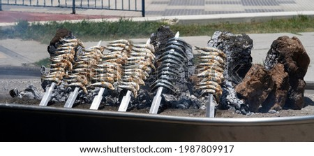 skewers of sardines over incandescent and smoky embers in Malaga. Typical food for holidays and beach in Spain. Stockfoto ©