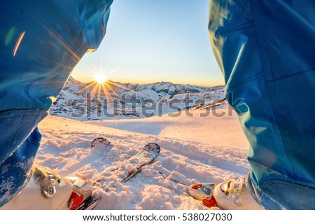 Ski athlete standing in front of wonderful sunset  on top of the mountain - Legs view of young skier with sun back light - Sport and vacation concept - Focus on skis - Warm filter #538027030