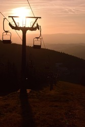 Ski chair lift in the mountains at pink sunrise. Vertical photo.