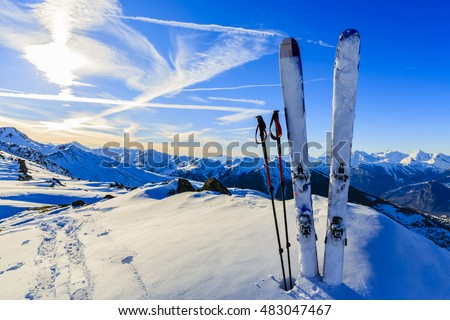 Ski in winter season, mountains and ski touring equipments on the top at sunrise.