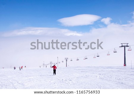 Ski lift and ski slope with skiers under it on sunny winter day with blue sky. #1165756933
