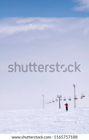 Ski lift and ski slope with skiers under it on sunny winter day with blue sky. #1165757188