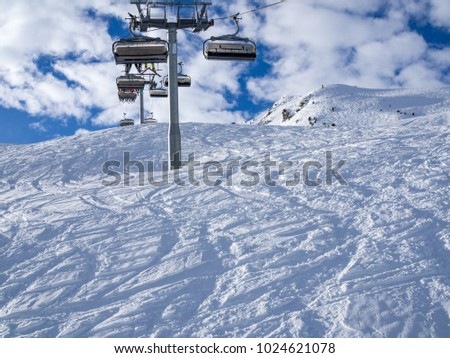 Ski lift and ski slope with skiers under it on sunny winter day with blue sky. Alpine resort Meribel, France. Europe, january, 2018 #1024621078