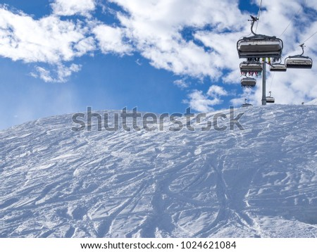 Ski lift and ski slope with skiers under it on sunny winter day with blue sky. Alpine resort Meribel, France. Europe, january, 2018 #1024621084