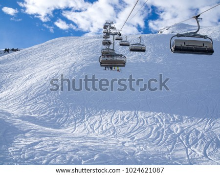 Ski lift and ski slope with skiers under it on sunny winter day with blue sky. Alpine resort Meribel, France. Europe, january, 2018 #1024621087